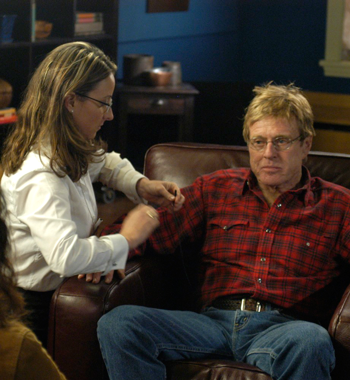 Jennifer Smith helping Robert Redford on set before she started her corporate wellness company.